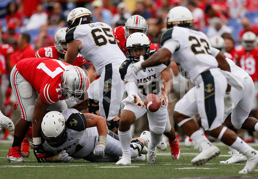 Ohio State Buckeyes defensive lineman Michael Hill (77) tries to get to Navy Midshipmen quarterback Tago Smith (18) during Saturday's NCAA Division I football game at M&T Bank Stadium in Baltimore on August 30, 2014. Ohio State won the game with a final score of 34-17. (Dispatch Photo by Barbara J. Perenic)