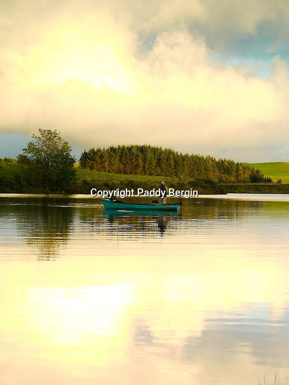 This photo was taken at Llyn Frongoch in close proximity to the village of Trisant, close to the Aberystwyth to Devil&rsquo;s Bridge road. Frongoch is a fly only lake and is regularly stocked with both brown and rainbow trout. The quality of fish is excellent and boats are available. At Frongoch, Aberystwyth Angling Association have two caravans for hire for visitors wishing to stay in the area and take advantage of the fishing in this small but delightfully situated lake. Admist wonderful upland scenery, close to the Rheidol and Ystwyth valleys, and just twelve miles from the coast at Aberystwyth they represent excellent value for anyone wishing to combine angling with a family holiday. <br /> <br /> Stock Photo by Paddy Bergin