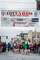 Aliy Zirkle and team leave the ceremonial start line with an Iditarider at 4th Avenue and D street in downtown Anchorage, Alaska during the 2015 Iditarod race. Photo by Jim Kohl/IditarodPhotos.com