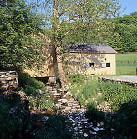 A rock-strewn stream runs under part of this converted barn in the grounds of the property