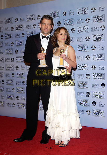 CLIVE OWEN & NATALIE PORTMAN.62nd Annual Golden Globe Awards at The Beverly Hilton Hotel Hotel, Los Angeles, California. Pressroom.January 16th, 2005 .full length, award trophy, tuxedo, white dress, profile, arm aroung waist, wide black belt ruffles layers.www.capitalpictures.com.sales@capitalpictures.com.©Capital Pictures