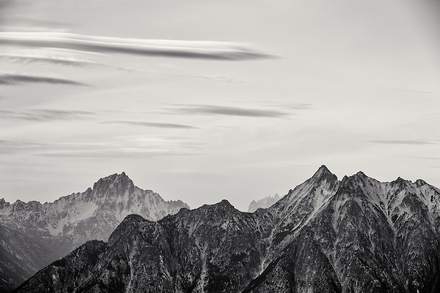 Lenticular clouds form over Golden Horn and Tower Mountain in this duotone black and white scene in Washington's North Cascade mountain range.