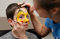 NWA Democrat-Gazette/DAVID GOTTSCHALK  Matthew Young, 8, has a Pikachu character painted on his face by Hannah Homes, with Art of Fun, Friday, January 11, 2019, during the annual Fayetteville Fraternal Order of Police Family Fun Night at the Chancellor Hotel in Fayetteville. Entertainment included magic by Joey Williams and Mike Bliss, appearances by characters Spiderman and Ariel,face painting, balloon animals and other activities. Funds raised from the event go to support the Shop with a Cop program, scholarships, youth activities and the fishing derby.