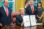 "United States President Donald J. Trump displays S. 3508, the ""Save Our Seas Act of 2018"" after signing it in the Oval Office of the White House in Washington, DC on Thursday, October 11, 2018.  Looking on from behind the President are: US Secretary of Commerce Wilbur L. Ross, Jr., left, US Senator Dan Sullivan (Republican of Alaska), center right, and Julie Fate, wife of Senator Sullivan, right.<br /> Credit: Ron Sachs / CNP"
