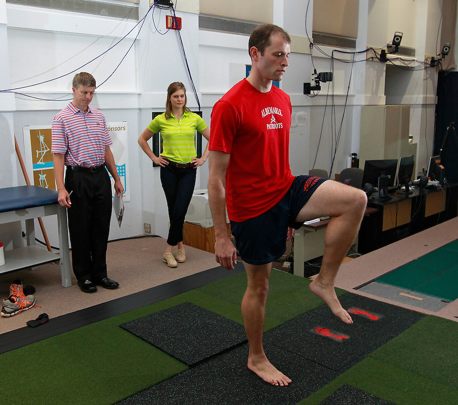 From left, director of the UVA SPEED Clinic Max Prokopy and biomechanical analyst Leigh Allin look at the form and balance of Matt Clay as he performs simple stretches during a visit to the clinic in Charlottesville, VA. Photo/Andrew Shurtleff