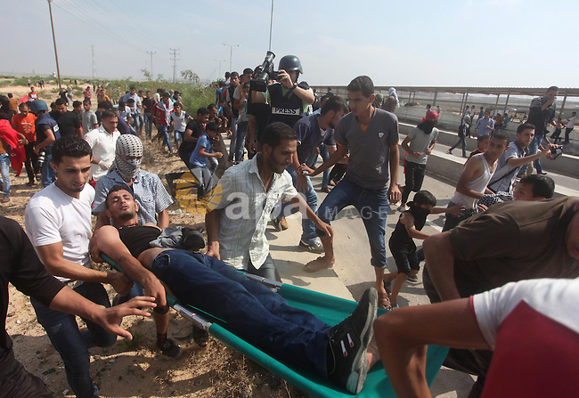 Palestinian protesters carry an injured comrade during clashes with Israeli security forces next to the border fence with Israel, at the Erez crossing in the northern Gaza strip, on October 13, 2015. A wave of stabbings that hit Israel, Jerusalem and the West Bank this month along with violent protests in annexed east Jerusalem and the occupied West Bank, has led to warnings that a full-scale Palestinian uprising, or third intifada, could erupt. The unrest has also spread to the Gaza Strip, with clashes along the border in recent days leaving nine Palestinians dead from Israeli fire. Photo by Ashraf Amra