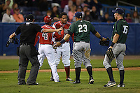 Batavia Muckdogs manager Angel Espada (4) holds back Carlos Duran (30) with umpire Christopher Stump, third baseman Kevin Ross (23) and outfielder Michael Suchy (35) getting in between after the benches cleared during a game against the Jamestown Jammers on July 25, 2014 at Dwyer Stadium in Batavia, New York.  Batavia defeated Jamestown 7-2.  (Mike Janes/Four Seam Images)