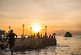 ZANZIBAR,Stone Town, Young Boys are playing and jumping to the Water from City's Wall during Sunset