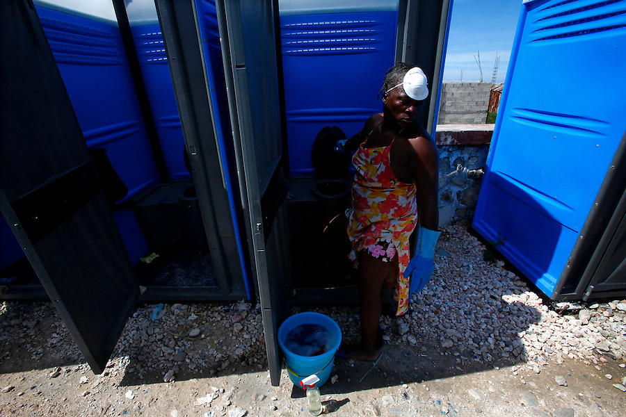 Nov 10, 2010 - Port-au-Prince, Haiti.A local resident of the Cite Soleil area of Port-au-Prince, Haiti reacts to the smell as she opens the door to a portable toilet inside a tent city to clean it on Wednesday, November 10, 2010 as fears of a Cholera outbreak spread through the area just two days after cases of the infection were confirmed in the area, the poorest slum in Haiti's capital. Officials from the Pan American Health Organization warn that Haiti's cholera epidemic, spread primarily through consuming infected water and food, is likely to grow much larger in the wake of Hurricane Tomas.  (Credit Image: Brian Blanco/ZUMA Press)
