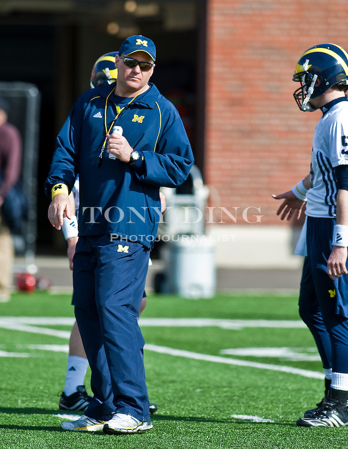 Michigan head coach Rich Rodriguez listens to quarterback Tate Forcier, right, during drills on the first day of spring football practices, Tuesday, March 16, 2010, in Ann Arbor, Mich. (AP Photo/Tony Ding)