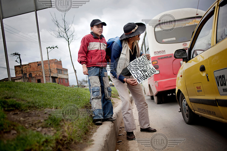 A displaced (IDP) man and his son beg for money from passing traffic in the slum neighbourhood of Soacha, south of Bogota.This story by Mads Nissen was partly funded by a grant and when published it should be credited: Funding for this project was provided by the Manuel Rivera-Ortiz Foundation for International Photography.