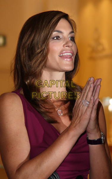 CINDY CRAWFORD .at a photocall to launch the new Omega watch collection at Westfield Shopping Centre, London, England, UK, .October 15th 2009.half length purple silver clear stone necklace profile ring hands together clapping gesture matching sleeveless wrist watch .CAP/JIL.©Jill Mayhew/Capital Pictures