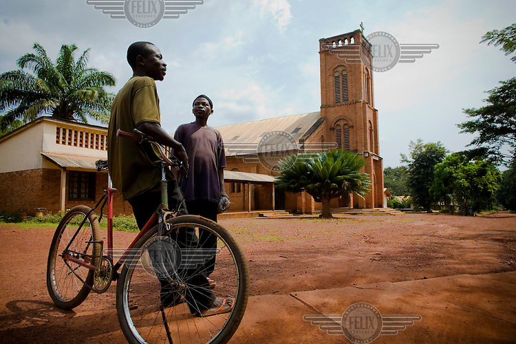 A man leaning on his bicycle stands talking to another man next to the Roman Catholic church.