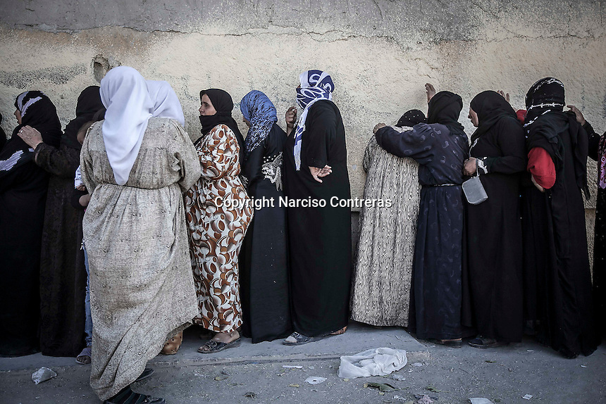 Syrian women queue for bread at a bakery in downtown Manbij, a city located at the northeast of Aleppo province.
