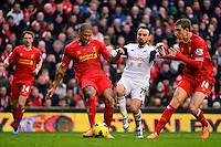 Sunday, 23 February 2014<br /> Pictured: Swansea City's Leon Britton competes with Liverpool's Glen Johnson and Jordan Henderson<br /> Re: Barclay's Premier League, Liverpool FC v Swansea City FC v at Anfield Stadium, Liverpool Merseyside, UK.