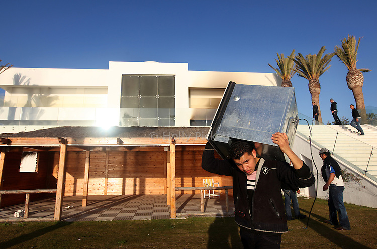 Looters gather furniture from a home of a relative of Tunisian President Zine el-Abidine Ben Ali, in Hammamet, Tunisia, about an hour's drive from the capital of Tunis, Thursday, Jan. 13, 2011. Tunisia has been rocked by violent protests which began nearly one month ago.