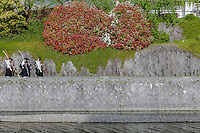 School boys carrying archery equipment, walk along the sides of the Kamo River looking at smartphones in Gion, Kyoto, Japan. Sunday April 24th 2016