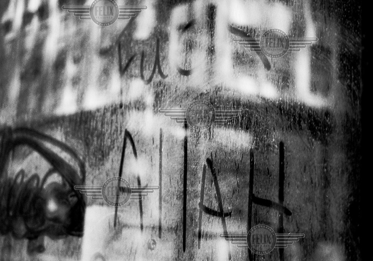 Grafitti written in the dust from the WTC fallout on the window of an office building in lower manhattan. September 15, 2001.