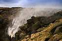 11/01/15<br /> <br /> Two hikers stop to take a photograph standing in the spray above Kinder Downfall as the 30 metre waterfall is blown back up on to the Kinder Plateau as 65mph gusts of wind batter the Derbyshire Peak District near Hayfield.<br /> <br /> All Rights Reserved - F Stop Press. www.fstoppress.com. Tel: +44 (0)1335 300098