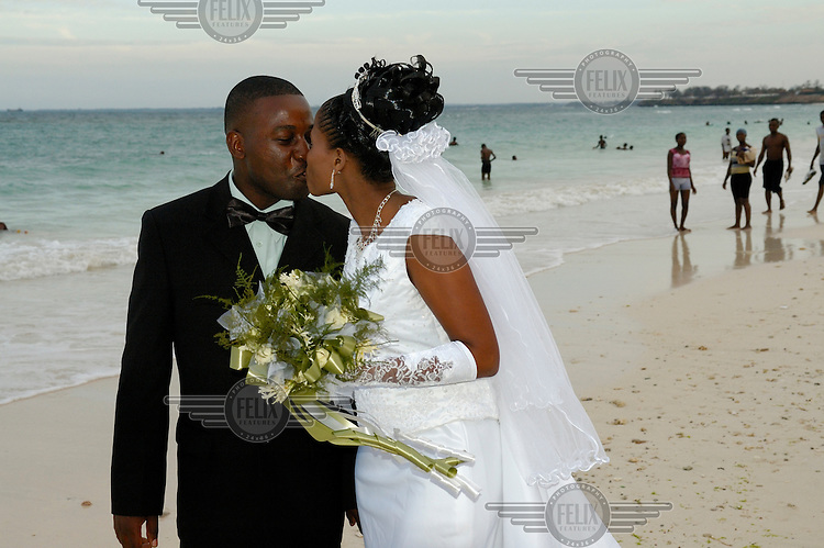 Couple kissing on Coco Beach (also known as Oyster Bay Beach) after their wedding.