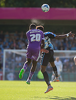Sweat flies off the heads of Hiram Boateng of Plymouth Argyle & Gozie Ugwu of Wycombe Wanderers as they go up for the ball in the afternoon sun during the Sky Bet League 2 match between Wycombe Wanderers and Plymouth Argyle at Adams Park, High Wycombe, England on 12 September 2015. Photo by Andy Rowland.