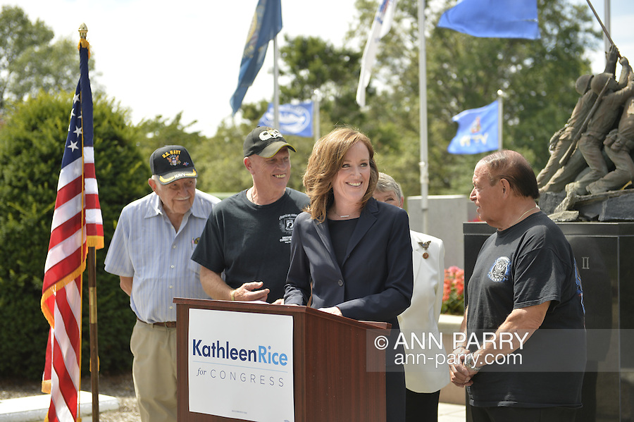 East Meadow, New York, U.S. - September 3, 2014 - KATHLEEN RICE, at podium, Democratic congressional candidate (NY-04), releases a whitepaper on veterans policy and announces formation of her campaign's Veterans Advisory Committee, at Veterans Memorial at Eisenhower Park, after touring Northport VA Medical Center with outgoing Rep. CAROLYN MCCARTHY (behind Rice, in white jacket). Congresswoman McCarthy and several committee members joined Rice at the press conference, including: PAUL ZYDOR, (in blue shirt) of Merrick, U.S. Navy, Korean War Veteran; PAT YNGSTROM, (in black T-shirt and cap) of Merrick, U.S. Army Paratrooper, Vietnam War Veteran; STEVE BONOM, (in black T-shirt and pants) of Massapequa, U.S. Navy, Vietnam War Veteran. Rice is in her third term as Nassau County District Attorney, Long Island.