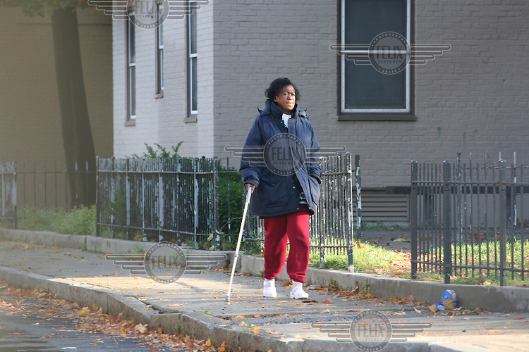 Zeituni Onyango, the aunt of Barack Obama, walks outside her home in a  housing project in south Boston. Exclusive picture taken by Tom Pilston / Panos for the Times.