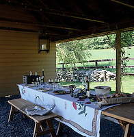 A rustic table is laid for an impromptu lunch in a rustic loggia