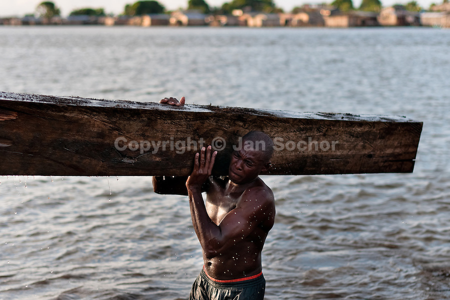 A Colombian worker carries a heavy timber from the Pacific rainforest at a sawmill in Tumaco, Colombia, 15 June 2010. Tens of sawmills located on the banks of the Pacific jungle rivers generate almost half of the Colombia's wood production. The wood species processed here (sajo, machare, roble, guabo, cargadero y pacora) are mostly used in the construction industry and the paper production. Although the Pacific lush rainforest in Colombia is one of the most biodiverse area of the world, the region suffers an extensive deforestation due to the uncontrolled logging in the last years.
