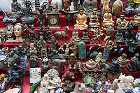Buddha statues and ornaments for sale at a street market stall in Yangshuo, Guangxi, China.