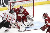 Denver's Paul Phillips is able to poke the puck away from UNO's Zahn Raubenheimer as goalie Sam Brittain defends the goal. Denver beat Nebraska-Omaha 4-2 Saturday night at Qwest Center Omaha. (Photo by Michelle Bishop)