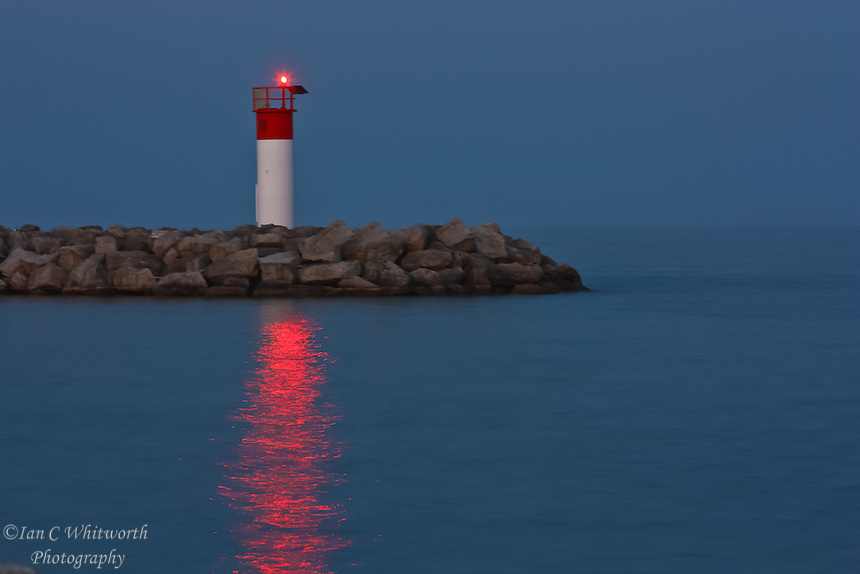 A view of the Bronte Harbour lighthouse and it's light reflection in the water at dusk