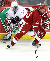 Wisconsin's Craig Smith works the puck while being pressured by UNO's Alex Hudson. No. 16 UNO beat No. 7 Wisconsin 4-1 in front of a school-record crowd of 15,137 Friday night at Qwest Center Omaha.  (Photo by Michelle Bishop)