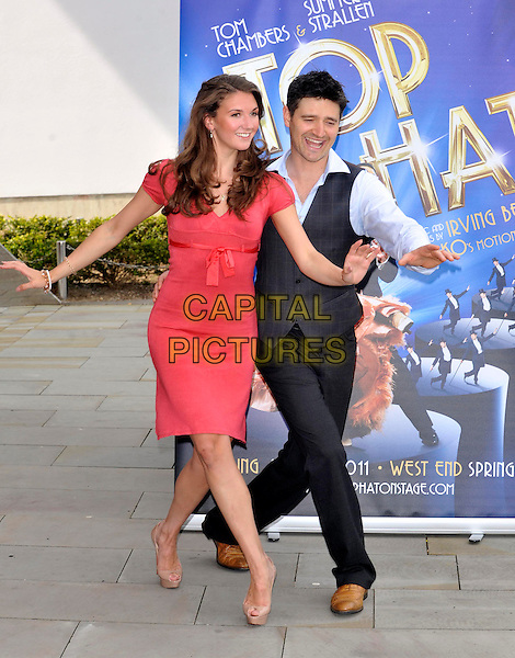 TOM CHAMBERS & SUMMER STRALLEN .Photocall to Launch a new production of 'Top Hat the Musical' at Milton Keynes Theatre, Bucks, UK, May 6th 2011..full length red sleeveless dress dancing pose waistcoat suit blue shirt  beige nude christian louboutin shoes heels hands bow pink grey gray .CAP/JIL.©Jill Mayhew/Capital Pictures