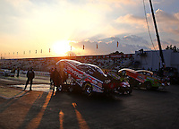 Feb 7, 2014; Pomona, CA, USA; The sun sets behind the grandstands as NHRA funny car drivers Courtney Force (near lane) and Bob Bode sit in the water box during qualifying for the Winternationals at Auto Club Raceway at Pomona. Mandatory Credit: Mark J. Rebilas-