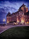 Artistic dramatic photo of Fairmont Le Château Frontenac castle illuminated with street lights at night with dramatic nlue sky, grand hotel Chateau Frontenac, National Historic Site of Canada. Old Quebec City, Quebec, Canada. Ville de Québec.