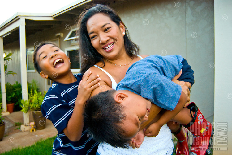 Local part Hawaiian mom and 2 young sons in front yard of home in Makakilo, Oahu