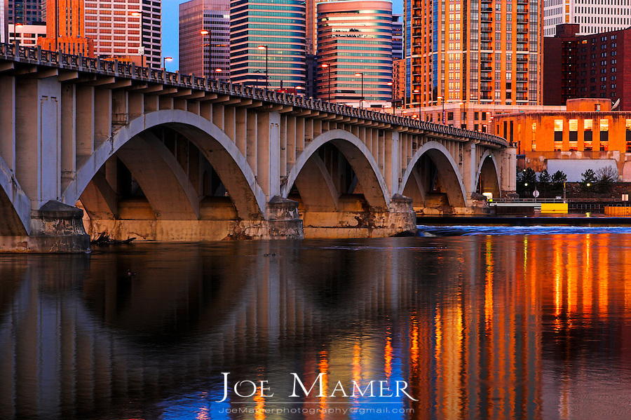 Downtown Minneapolis at sunrise viewed across the Mississippi river.