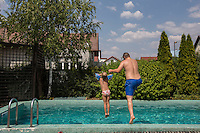 Romania - Timisoara - Adrian Ionescu jumping in the pool of the Live Cams Mansion with his daughter. Adrian is the manager of the Mansion.