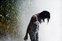 A Haitian gilr performs a bathing and cleaning ritual under the waterfall during the annual religious pilgrimage in Saut d'Eau, Haiti, July 16, 2008. Every year in summer thousands of pilgrims from all over Haiti make the religious journey to the Saut d'Eau waterfall (100km north of Port-au-Prince). It is believed that 150 years ago the spirit of Virgin Mary (Our Lady of Mount Carmel) has appeared on a palm tree close to the waterfall. This place became a main pilgrimage site in Haiti since then. Haitians wearing only underwear perform a bathing and cleaning ritual under the 100-foot-high waterfall. Voodoo followers (many Haitians practise both voodoo and catholicism) hope that Erzulie Dantor, the Voodoo spirit of water, manifest itself and they get possessed for a short moment, touched by her presence.