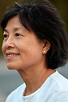 Asian woman smiling, husband in background