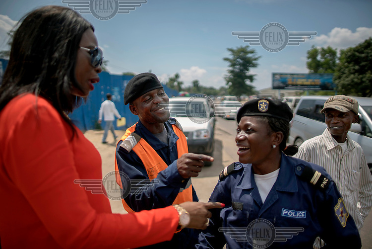 Therese Kirongozi (left), speaks to Kinshasa traffice police officers. <br /> Women's Tech, a small enterprise started by Therese Kirongozi, a local entrepreneur, manufactures humanoid traffic robots that are intended to blend the functions of traffic lights with human traffic police officers to control and monitor traffic flow. They are solar powered, equipped with green and red lights and can play pre-recorded messages to pedestrians to let them know when it's safe to cross the street. They also have in-built video cameras which convey footage back to a central office where it is evaluated and used to enhance traffic flow in the city and to prosecute traffic offences.