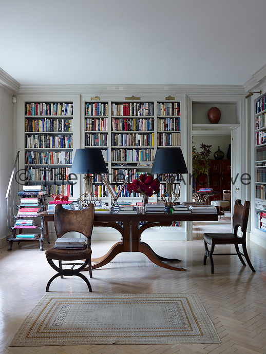 In the library a pair of English Regency chairs is placed beside a contemporary mahogany table designed by Rose Tarlow