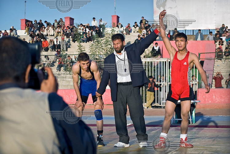 The referee declares the winner of a match at the Olympic Stadium in Kabul, where the national wrestling championship is taking place. Young men from across the provinces have come to Kabul to participate.