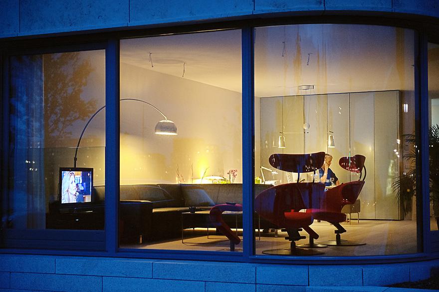 Nederland, Amsterdam, 10 juli 2012.Woning met grote open ramen waardoor je het interieur goed kan zien. Veel mensen doen geen gordijnen dicht zodat je goed naar binnen kunt kijken..Tv staat aan, maar niemand kijkt..Foto (c): Michiel Wijnbergh