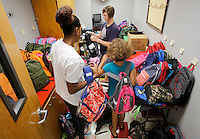 NWA Democrat-Gazette/DAVID GOTTSCHALK  Taylor Ellis-Watson (from left), Lynette Washington and her daughter Maiesha (cq), 8, organize backpacks filled with school supplies at Asbell Elementary School Monday, August 3, 2015 in Fayetteville. The three are participating in The Grove Church's fourth annual Packs for Life program which collects and donates age specific school supplies. Asbell Elementary School begins today.