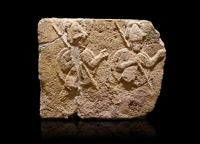 Hittite relief sculpted orthostat stone panel of Long Wall Limestone, Karkamıs, (Kargamıs), Carchemish (Karkemish), 900-700 B.C. . Anatolian Civilisations Museum, Ankara, Turkey.<br /> <br /> Two helmeted soldiers in short skirt carry shield on their backs and spear in their hands.<br /> <br /> On a black background.