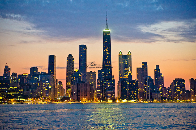 """Dusk view of Chicago's magnificent skyline as seen from Lake Michigan. The architecture of Chicago has influenced and reflected the history of American architecture. The city of Chicago, Illinois features prominent buildings in a variety of styles by many important architects. Since most buildings within the downtown area were destroyed by the Great Chicago Fire in 1871, Chicago buildings are noted for their originality rather than their antiquity..Beginning in the early 1880s, architectural pioneers of the Chicago School explored steel-frame construction and, in the 1890s, the use of large areas of plate glass. These were among the first modern skyscrapers and amongst their most famous architects were William LeBaron, John Wellborn Root Sr., Daniel Burnham and Charles Atwood. Louis Sullivan was perhaps the city's most philosophical architect. Realizing that the skyscraper represented a new form of architecture, he discarded historical precedent and designed buildings that emphasized their vertical nature. This new form of architecture, by Jenney, Burnham, Sullivan, and others, became known as the """"Commercial Style,"""" but it was called the """"Chicago School"""" by later historians..Since 1963, a """"Second Chicago School"""" emerged, largely due to the ideas of structural engineer Fazlur Khan. Some of Chicago's skyscrapers such as the John Hancock Center, Willis Tower (formerly known as the Sears Tower) and The Trump International Hotel and Tower are amongst the tallest buildings in the world."""