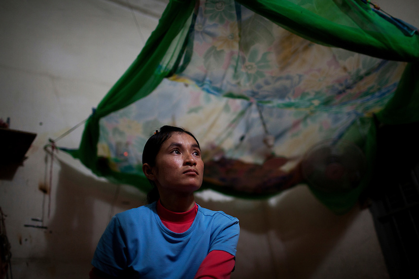 "Sorn Sreynoun, a 30-year-old worker at the Shen Zhou garment factory, sits in her rented room, which she shares with her sister, her sister's husband, and her nephew, Phnom Penh, Cambodia, Sept 14, 2011. Sorn Sreynoun has been working at Shen Zhou since 2005. Every six months she receives a new short-term contract, but there is no increase in the fixed salary (US$61 per month). She says she can earn around US$120 per month with overtime. The room costs US$40 per month, but she says before the salary increase in October 2010, it was cheaper. ""The price of the rented room always goes up when the fixed salary increases,"" she said ""It was US$30 before last October, then it went up to $35 and now it is $40 per month (after the rent was increased again a couple of months ago)."" Sorn Sreynoun spends around $30 dollars on food per month, and gets rice from her mother in their home province. ""The amount I spend depends on how much I eat and what kind of food. If I eat more delicious food, I will spend more."" She said ""If I eat less, my health will not be good and I won't be able to work properly. But if I eat more, I won't have money."" She has a 9-year-old son (who she sends money to support) living with her mother in Prey Veng province. Previously she was married, but her husband died 6 years ago, which is why she decided to get a job at a factory. ""Shen Zhou rarely has demonstrations because there are few problems. When we have problems, the workers will talk to our workers representative,"" she said."