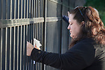 A woman prays along the fence surrounding the Federal Detention Center in Seatac, Washington, during a June 24 prayer vigil in support of immigrant parents inside the prison who've been separated from their children. The vigil was sponsored by the United Methodist Church.